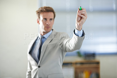 Buy stock photo Cropped shot of a handsome young businessman writing with a marker