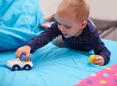 Buy stock photo A little boy playing with a toy car on his bed