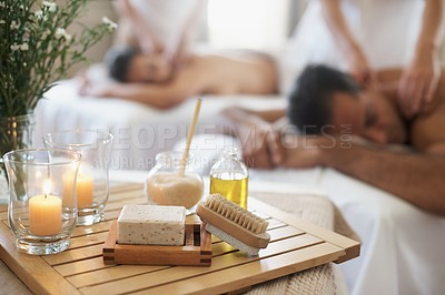 Buy stock photo Shot of an assortment of massage related products with a couple enjoying one in the background