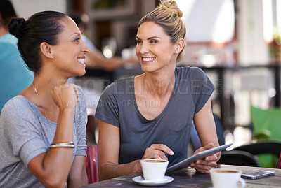 Buy stock photo Shot of two women sitting with a digital tablet at a cafe