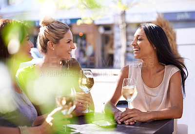Buy stock photo Cropped shot of three women enjoying a glass of white wine at a sidewalk cafe