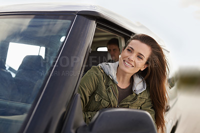 Buy stock photo Shot of an attractive young woman looking through the car window while on a road trip