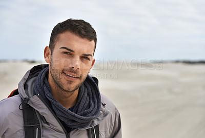 Buy stock photo Portrait of a young male hiker walking along the sand dunes