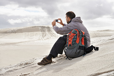 Buy stock photo Shot of a handsome male hiker sitting on the sand dunes and taking a photograph of the scenery