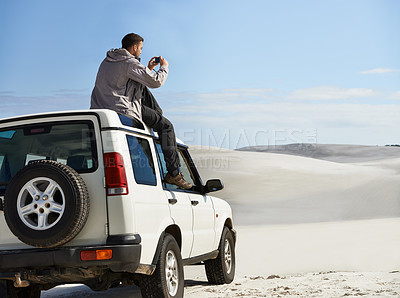 Buy stock photo Cropped shot of a young man sitting on his car roof while on a roadtrip