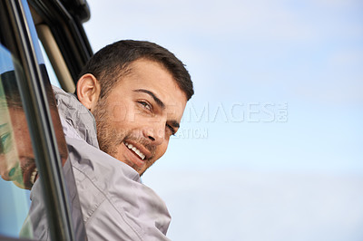 Buy stock photo Shot of a handsome young man looking back out the window of his car