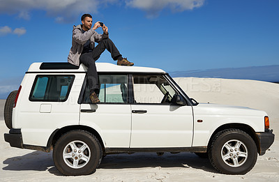 Buy stock photo Shot of a group of a man sitting on a car and taking a photo