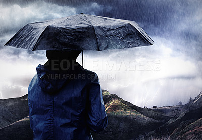 Buy stock photo Shot of a woman covered with an umbrella watching a thunderstorm over a mountain