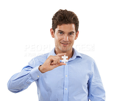 Buy stock photo Portrait of a handsome young man in a studio holding up a puzzle piece