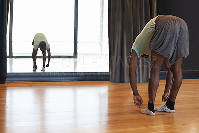 Buy stock photo Shot of a young male dancer stretching in a dance studio