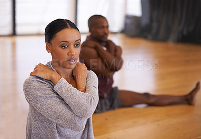 Buy stock photo Shot of a two young dancers stretching together in a studio