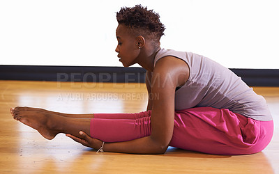 Buy stock photo Shot of a young woman stretching her legs in the dance studio
