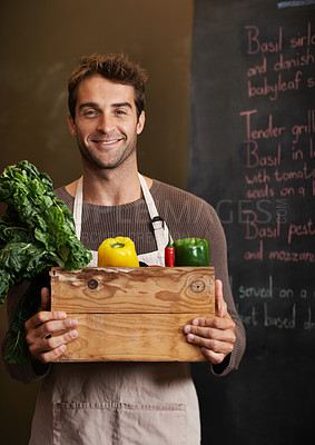 Buy stock photo Portrait of a young man holding a crate full of fresh vegetables