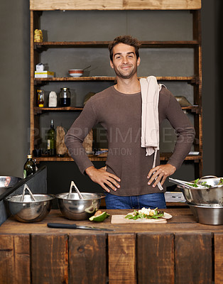 Buy stock photo Shot of a young man preparing a meal in his kitchen