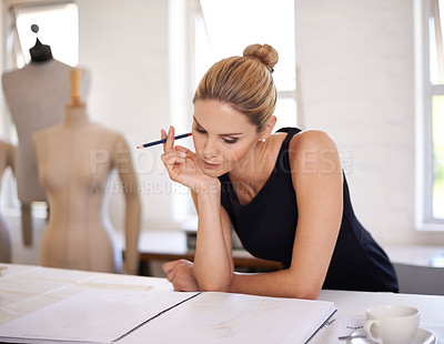Buy stock photo A fashion designer working on her sketches