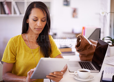 Buy stock photo A young businesswoman working on a digital tablet