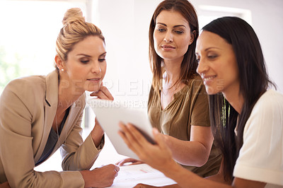Buy stock photo Three female colleagues having a discussion while gathered around a digital tablet