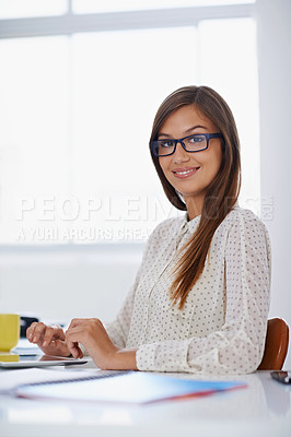 Buy stock photo Portrait of a young woman with glasses sitting at her workstation