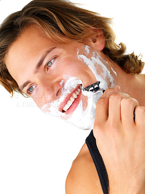Buy stock photo Portrait of a young handsome man shaving as part of his morning routine.