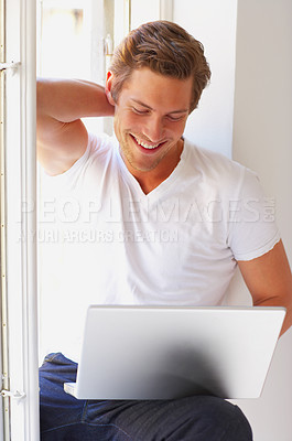 Buy stock photo A student relaxing and smiling with his laptop.