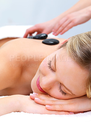 Buy stock photo Hot stone massaging with hands, smiling face - Portrait of a beautiful young girl at the day spa with black stones on her bare back