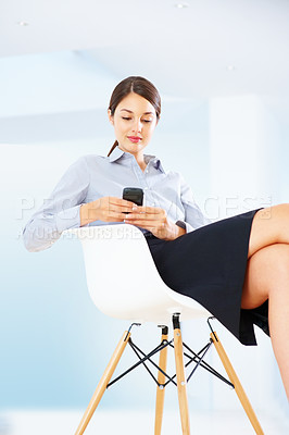 Buy stock photo Young female executive sitting on chair reading text message on her cellphone