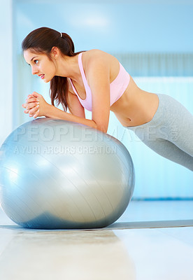 Buy stock photo Healthy young woman exercising with pilates ball