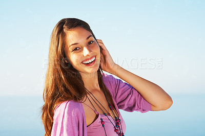 Buy stock photo Portrait of cute young woman standing against sky and smiling