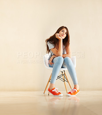 Buy stock photo Cute young woman sitting in a chair daydreaming about furnishing her first apartment while looking up into copyspace