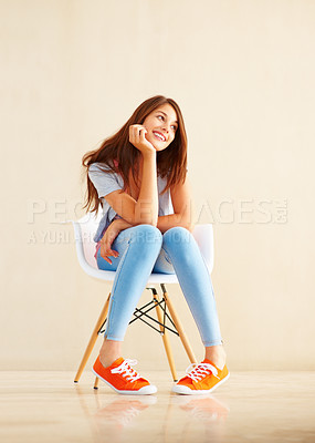Buy stock photo Full length of smiling young woman sitting on chair and looking away