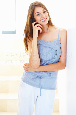 Buy stock photo Portrait of young smiling woman standing on staircase and leaning against wall