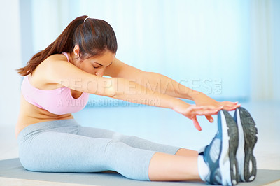 Buy stock photo Fit young woman stretching her legs and touching her feet