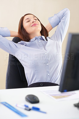 Buy stock photo Relaxed businesswoman sitting at an office table with hands behind head