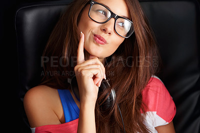 Buy stock photo Thoughtful young girl in glasses sitting on chair and looking away