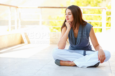 Buy stock photo Full length of thoughtful young woman sitting on terrace