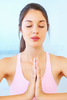 Buy stock photo Pretty young woman practicing yoga with hands joined and eyes closed