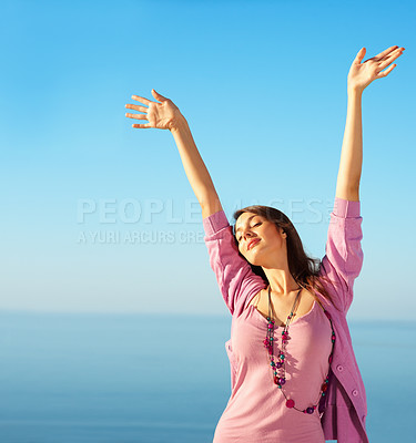 Buy stock photo Relaxed young woman with arms raised against sky - copyspace