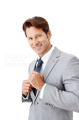 Buy stock photo Portrait of a happy young businessman fixing his necktie isolated against white background