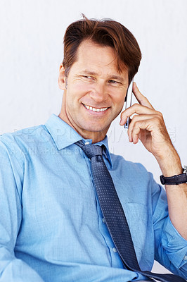 Buy stock photo Portrait of a happy young businessman speaking on cellphone against white background