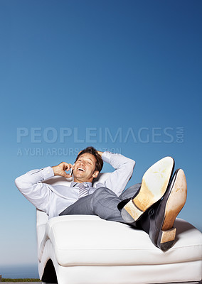 Buy stock photo Portrait of a relaxed male entrepreneur lying on a lawn chair and using cellphone against sky