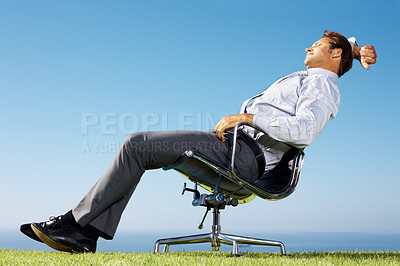 Buy stock photo Portrait of a young businessman resting on a chair in green field against sky
