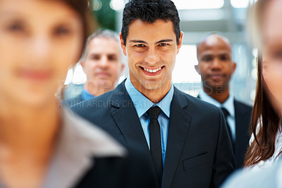Buy stock photo Focus on happy businessman with team in background