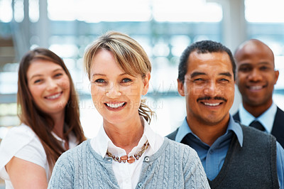 Buy stock photo Focus on female executive with team in background