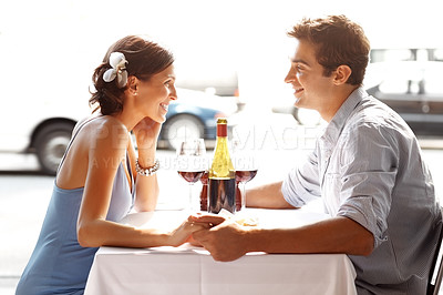 Buy stock photo Beautiful young couple in love sitting holding hands at restaurant