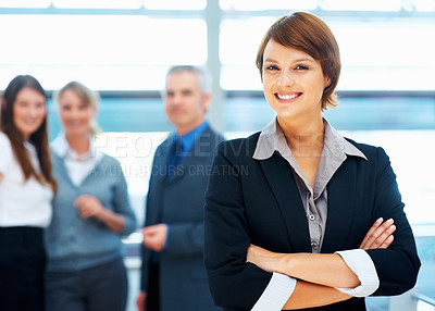 Buy stock photo Focus on pretty female executive with colleagues smiling in background