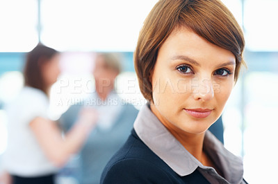 Buy stock photo Closeup view of female executive with colleagues in distance
