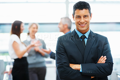 Buy stock photo Handsome executive with arms crossed and colleagues in distance