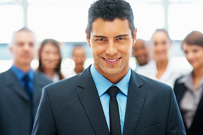 Buy stock photo Handsome executive with team in background