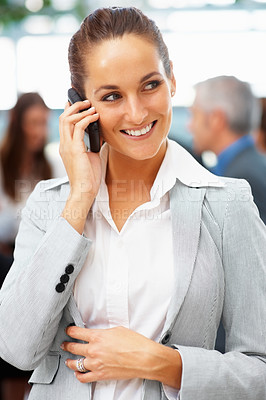 Buy stock photo Woman having a phone conversation with colleagues in background