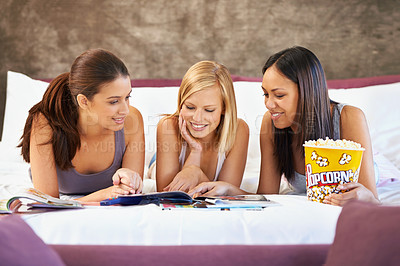 Buy stock photo Shot of a group of friends browsing through magazines while hanging out